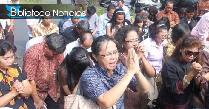 Cristianos indonesios adorando a Dios de rodillas en la calle